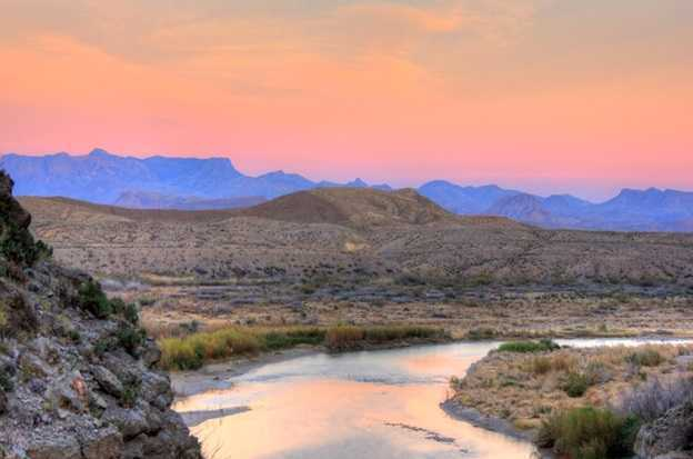Image shows the river flowing into the mountains around a bend at sunset in Big Bend National Park, Texas.