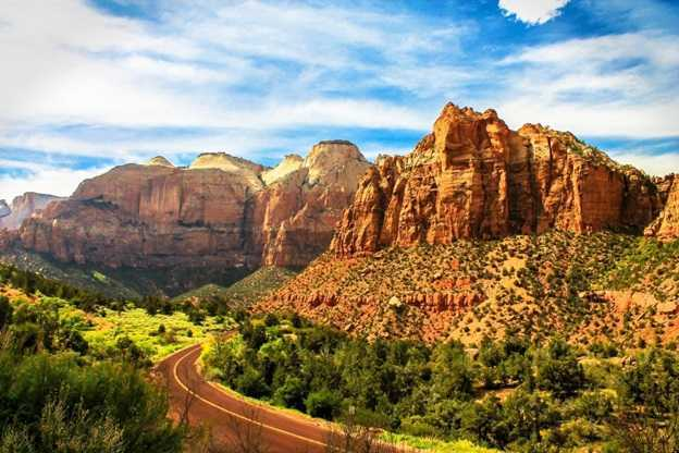 Image shows a two-lane roadway winding through the mountains in Zion National Park, Utah