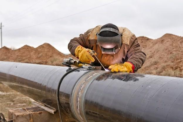 a man fixes the pipeline joint