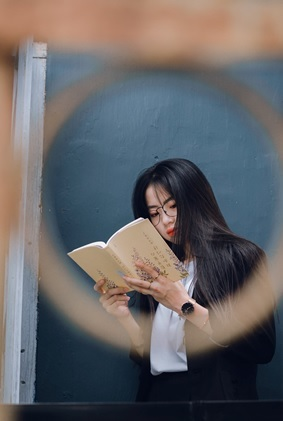girl standing reading a book