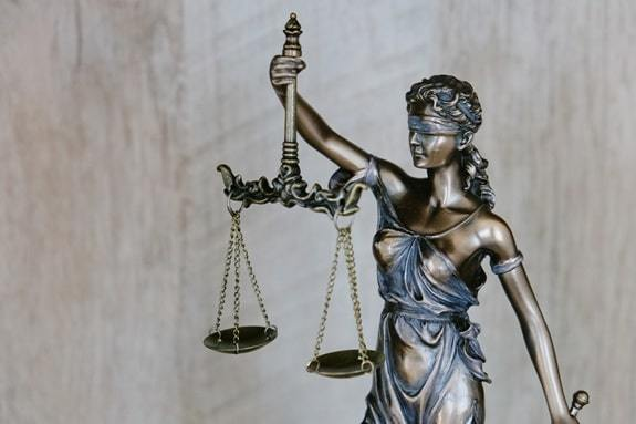 justitia blindfolded and holding a balance and a sword
