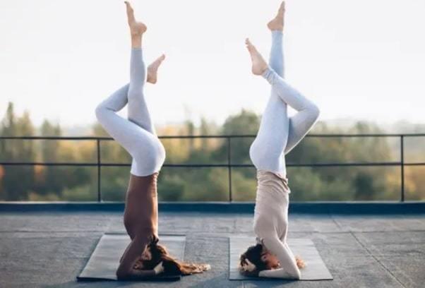 two young women doing double yoga asana