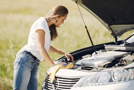 girl looking under car hood